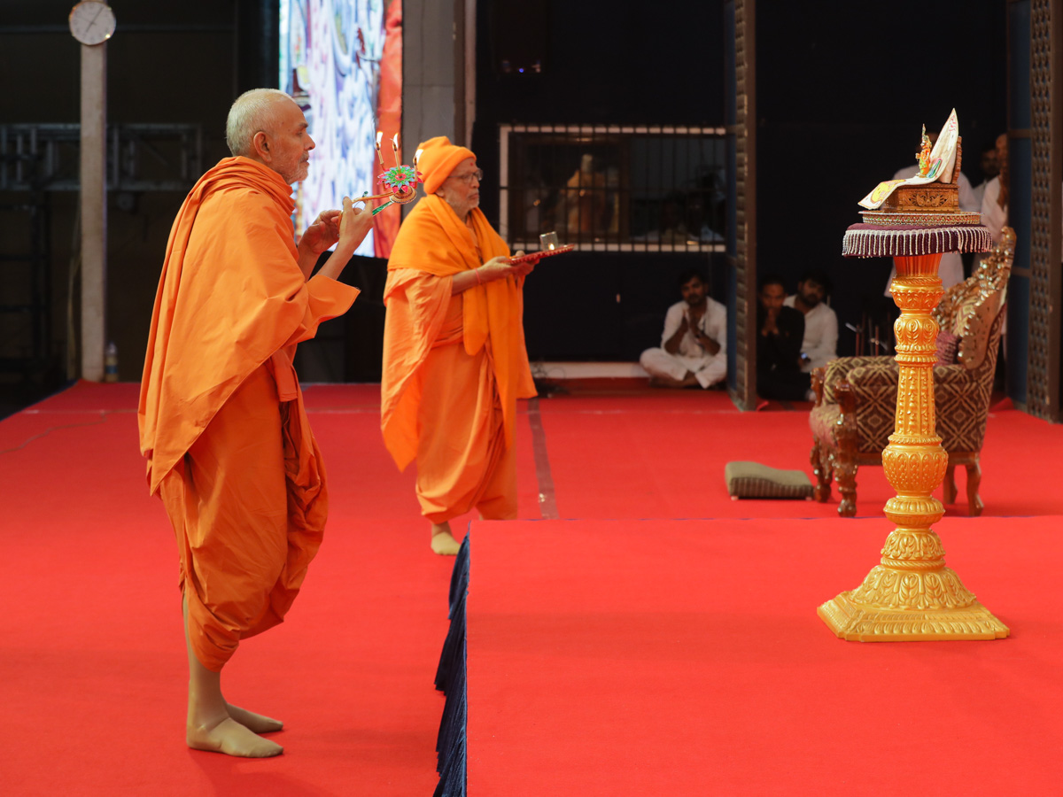 Swamishri and Pujya Ghanshyamcharan Swami perform the evening arti