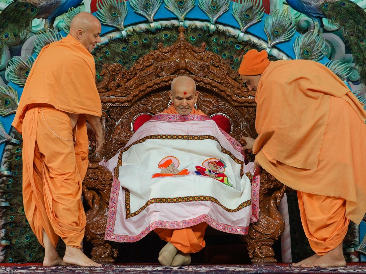 Pujya Viveksagar Swami and Atmaswarup Swami honor Swamishri with a shawl