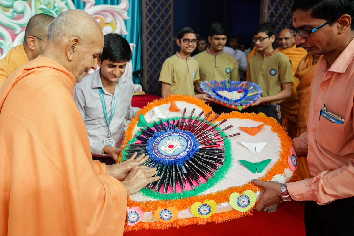 Swamishri sanctifies pens for students