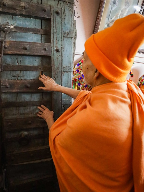 Swamishri reverentially touches the original door of Brahmaswarup Shastriji Maharaj's home