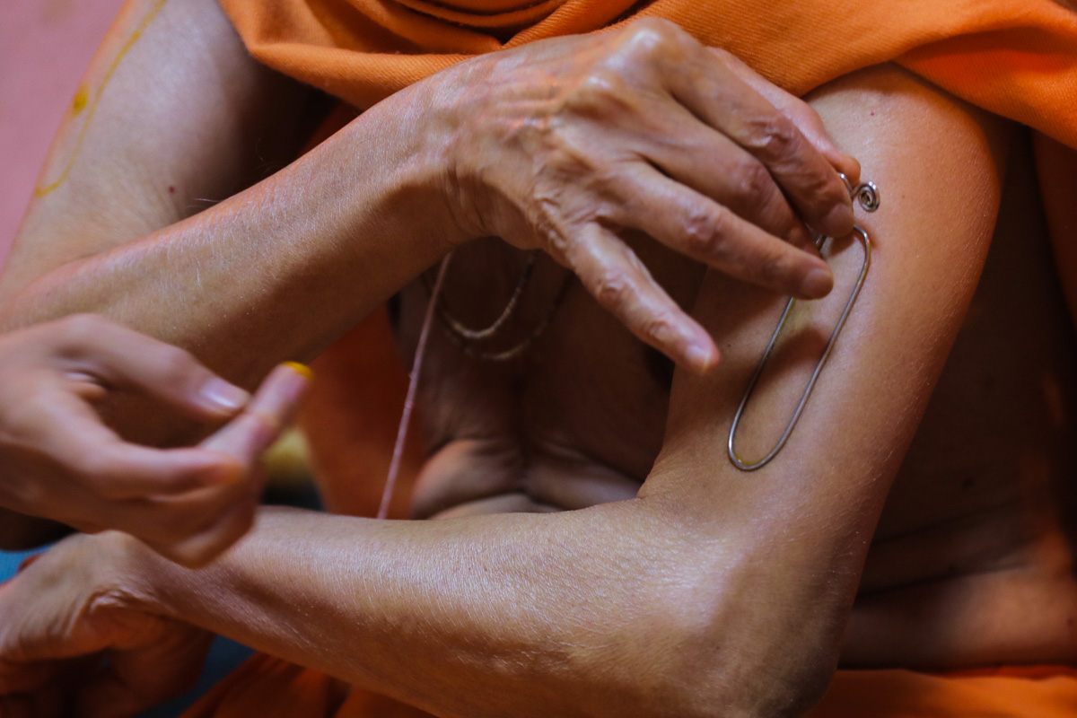 Swamishri applies tilak on his upper arm during his daily puja