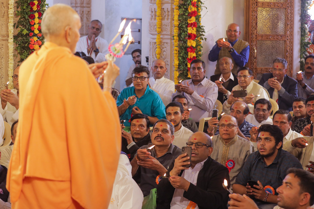 Swamishri and devotees perform the murti-pratishtha arti