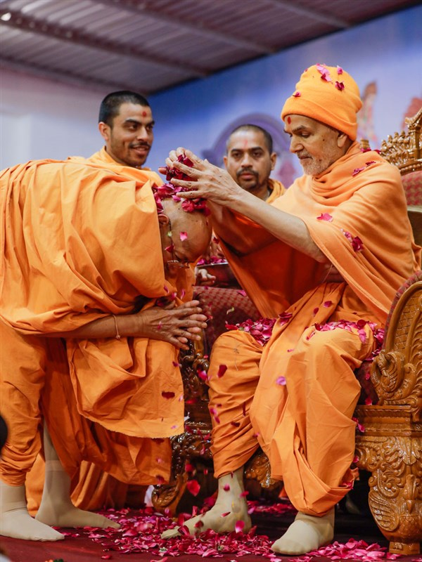 Swamishri showers flowers petals on Pujya Tyagvallabh Swami