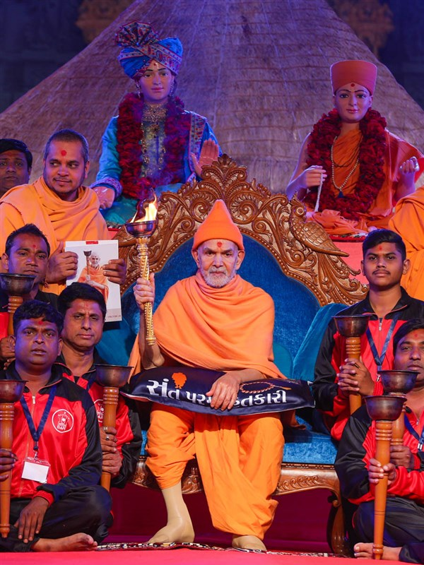 Swamishri holds the torch