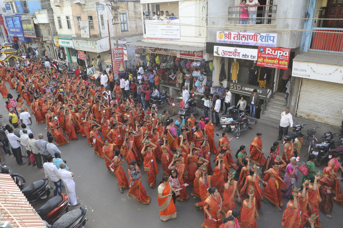 Women devotees carry kalashes and coconuts in traditional style during the procession