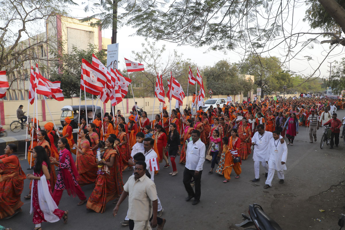 Women devotees in traditional dresses participate in the procession
