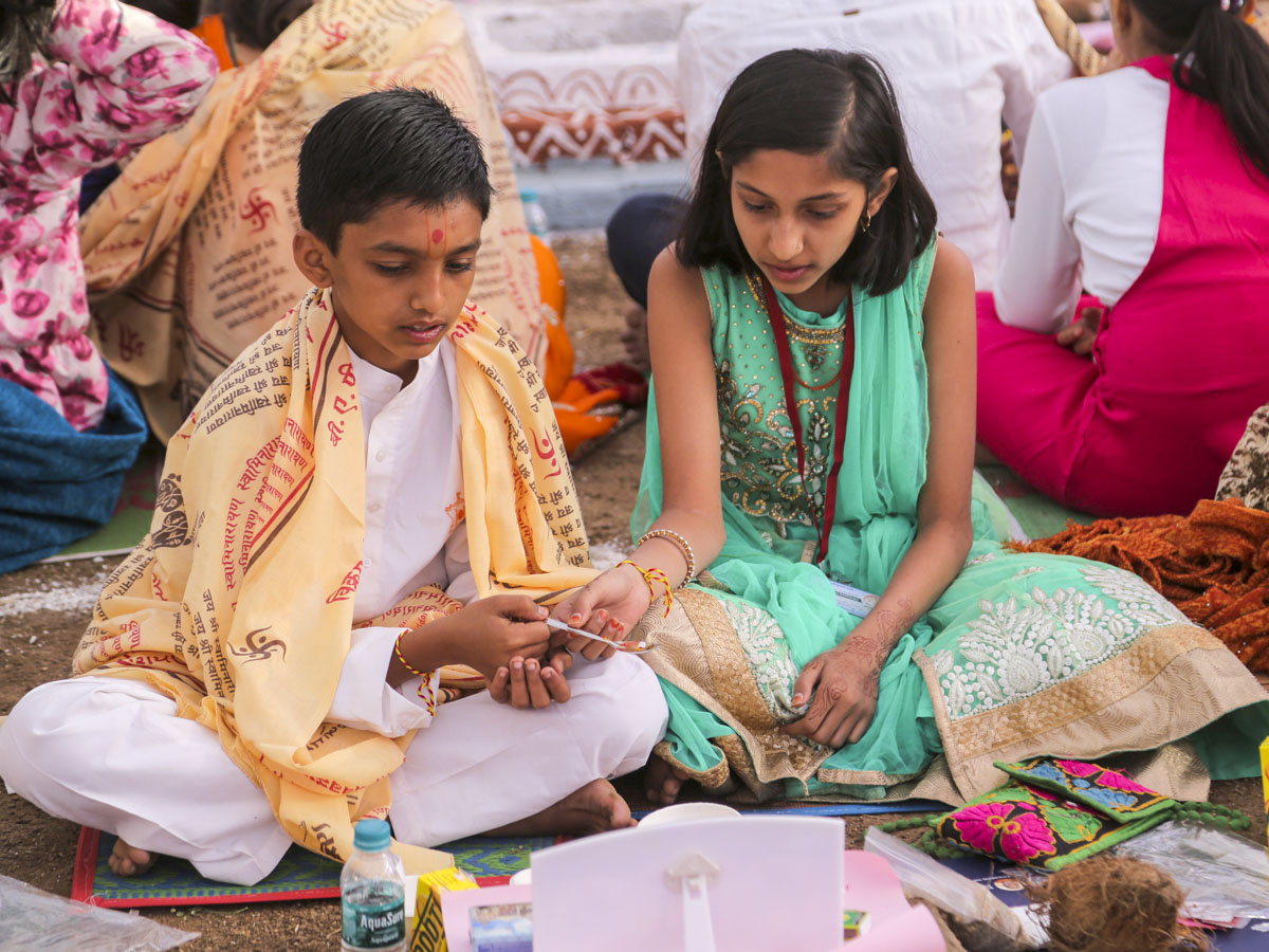 Children perform the yagna rituals