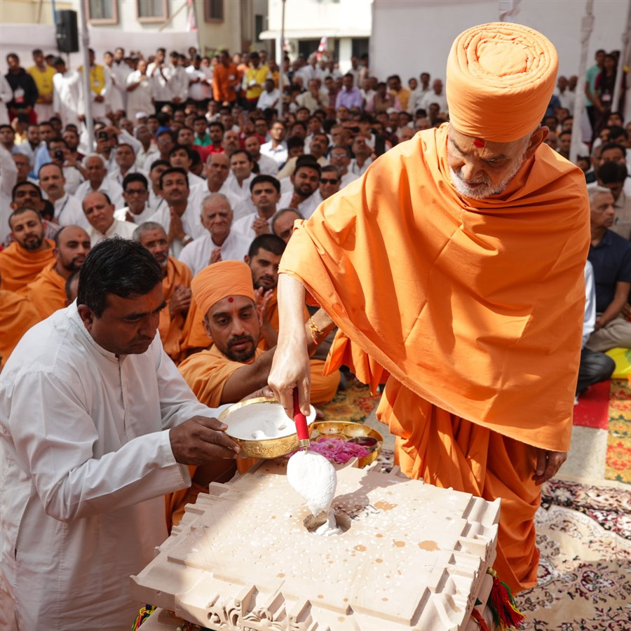 Swamishri fills the pillar with a special adhesive mixture