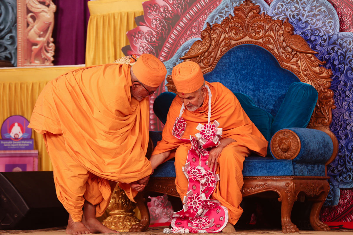 Pujya Kothari Swami honors Swamishri with a garland
