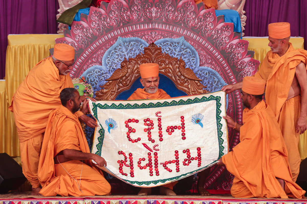 Pujya Kothari Swami, Pujya Viveksagar Swami and sadhus honor Swamishri with a shawl