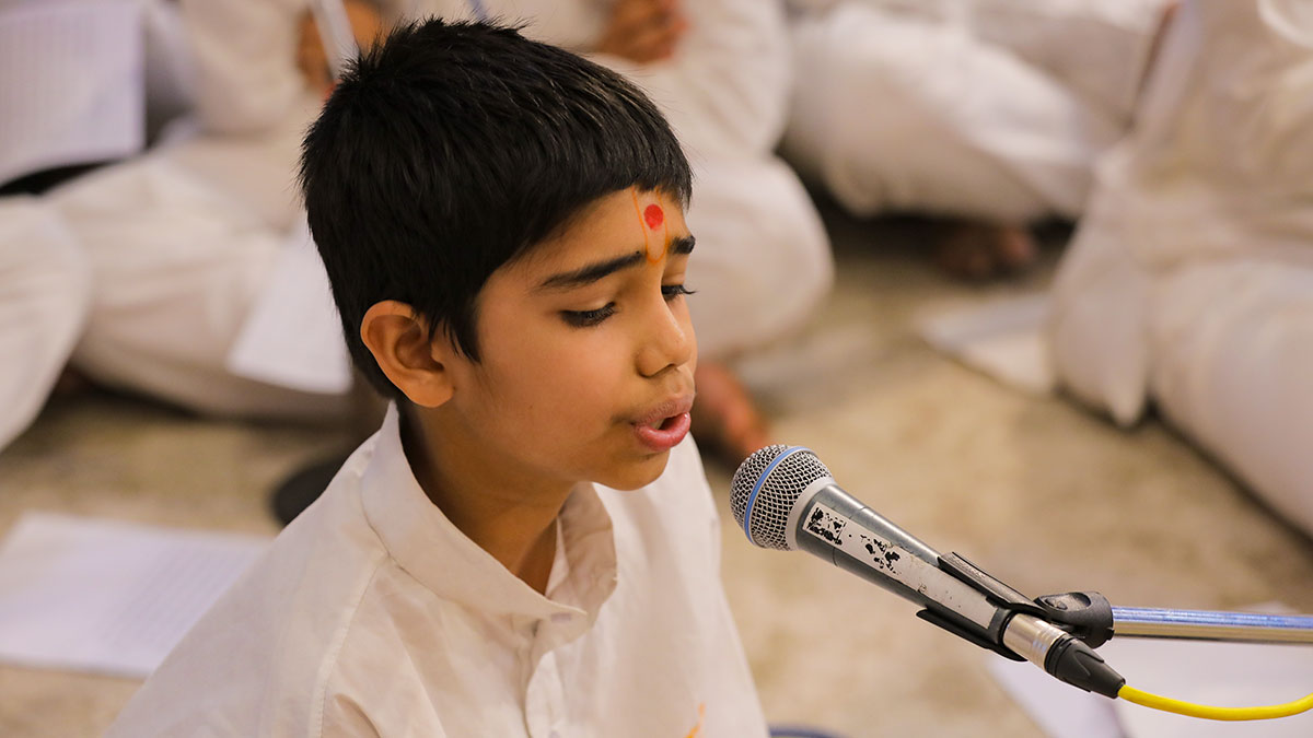 A child sings kirtans in Swamishri's morning puja