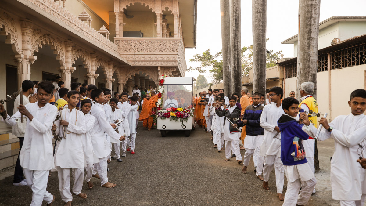 Children escort Swamishri while performing a lezim dance