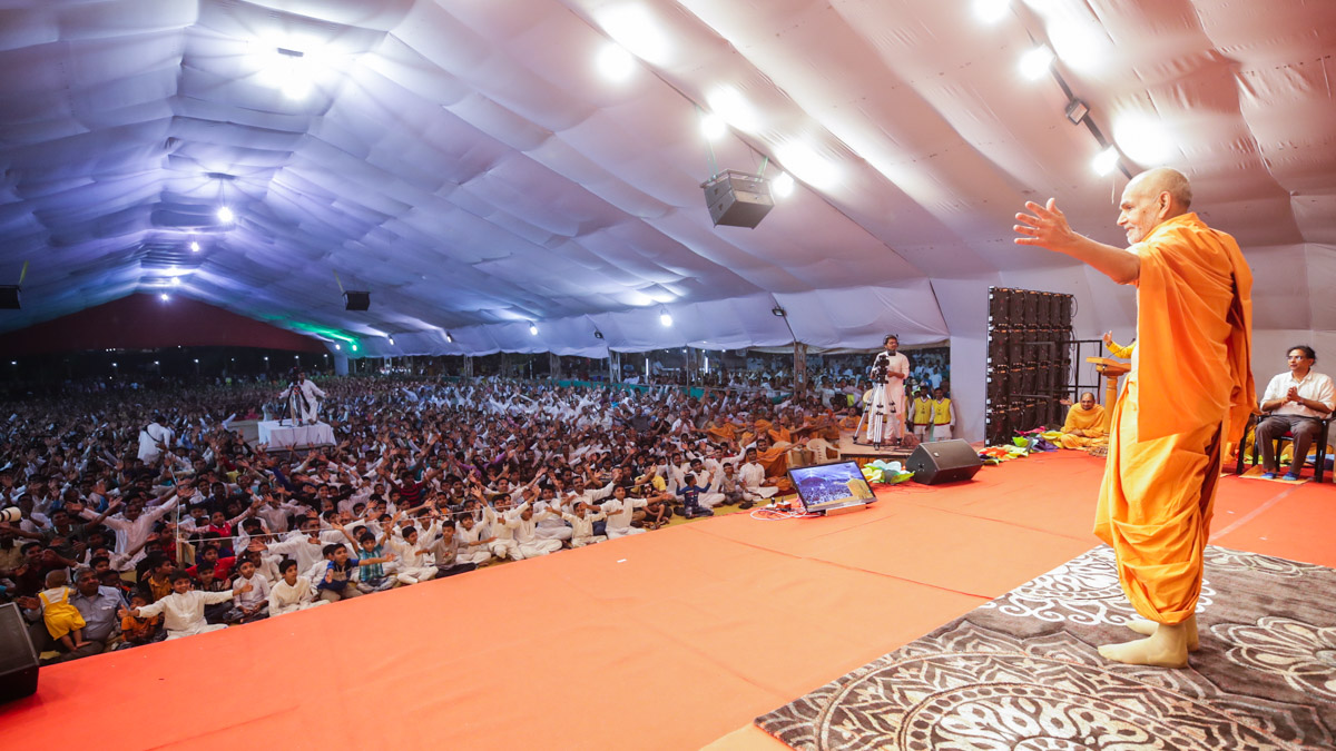 Swamishri gestures to embrace the devotees