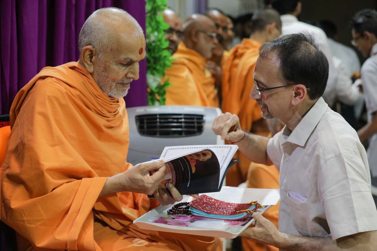 Swamishri sanctifies a school diary for the students