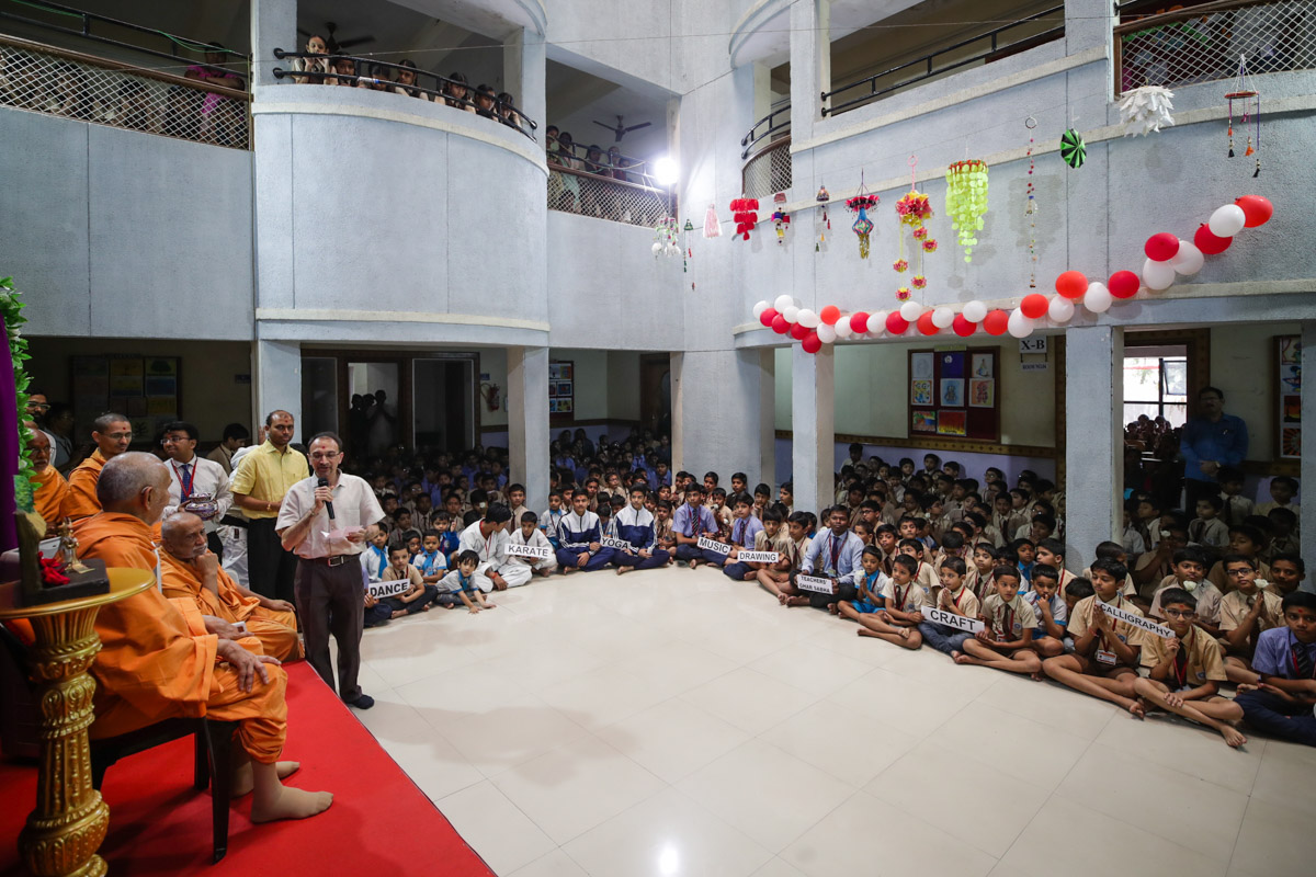 Swamishri listens to a report of the school and its activities