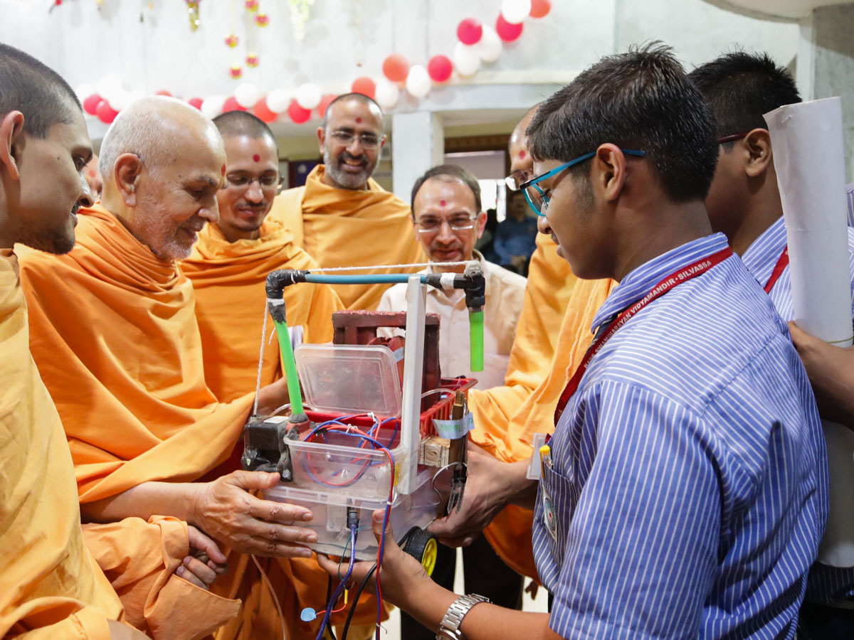 Swamishri observes a science project created by the students