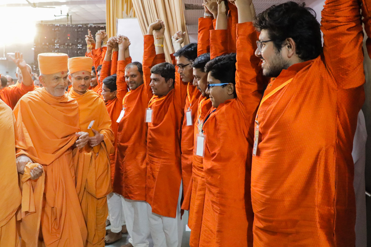 Youths join hands in a gesture of unity while Swamishri departs from Silvassa