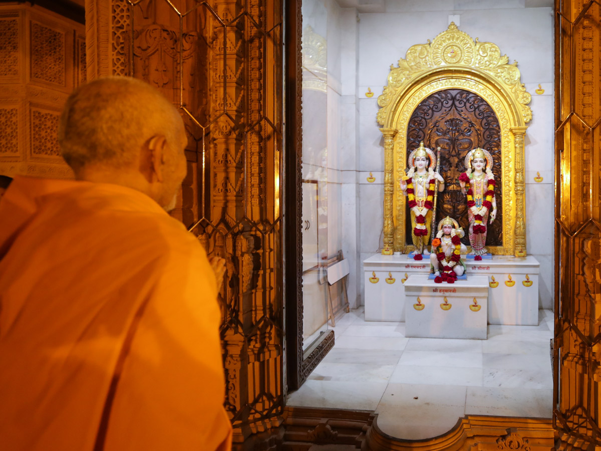 Swamishri engrossed in the darshan of Shri Sita-Ram Dev and Shri Hanumanji