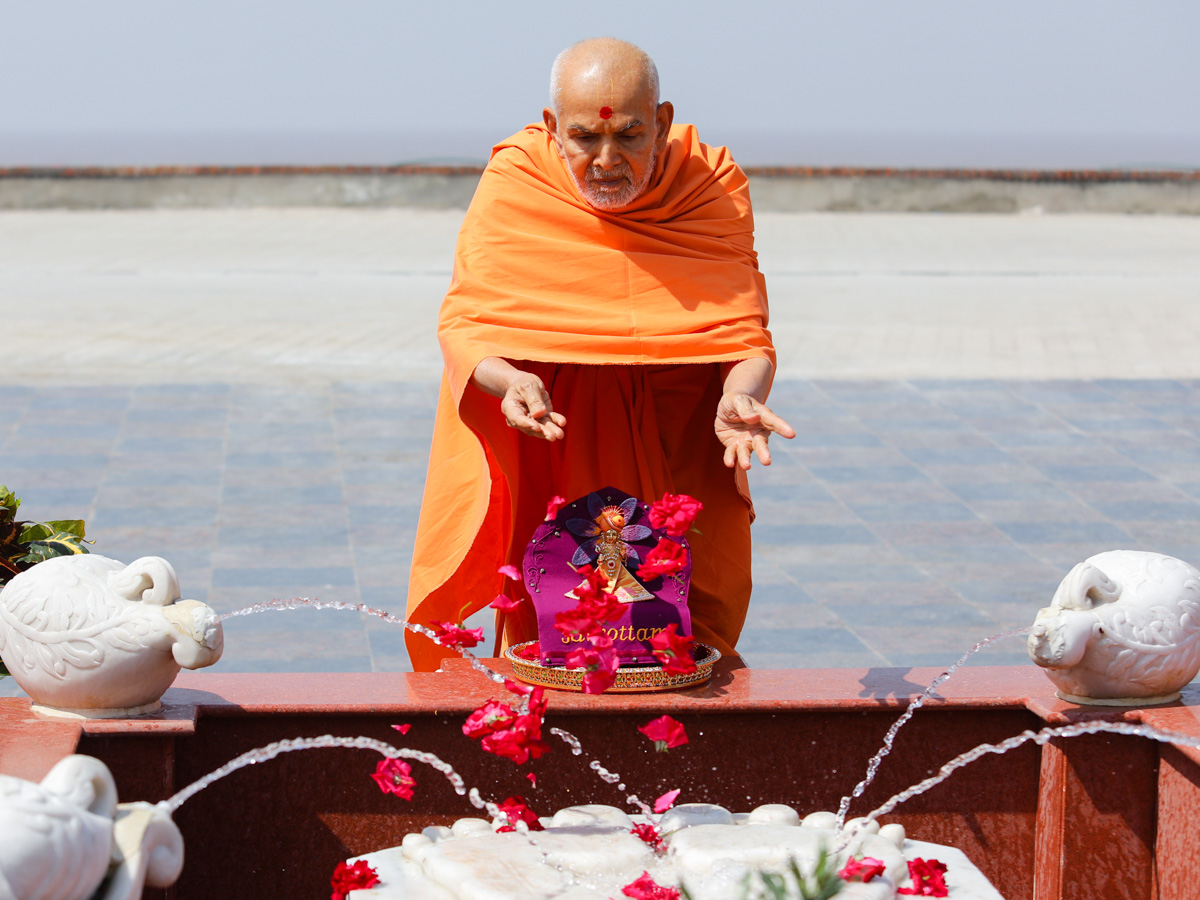 Swamishri showers flowers on the charanarvind