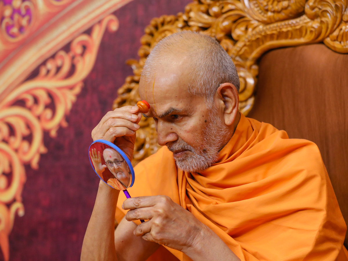 Swamishri applies chandlo on his forehead at the beginning of his daily puja