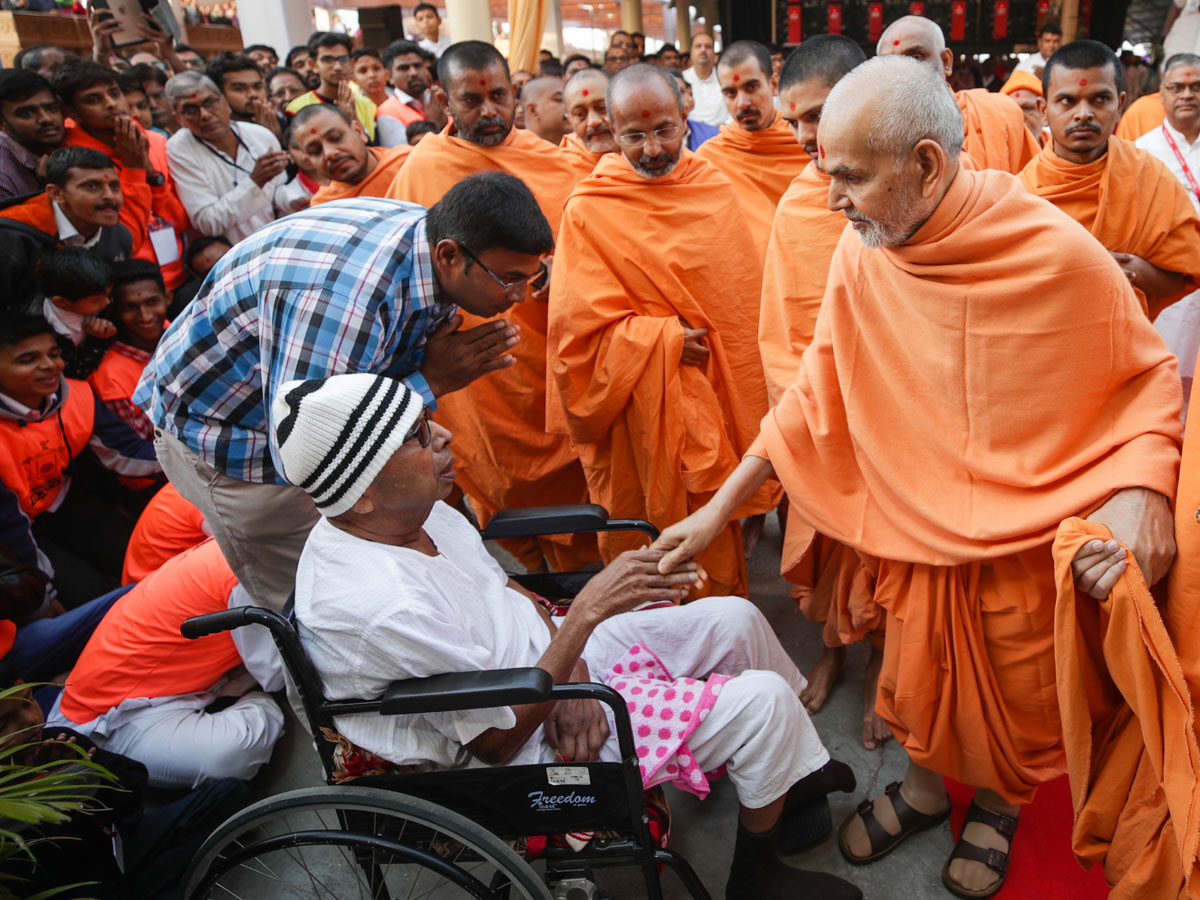 Swamishri blesses an ailing devotee in the mandir grounds