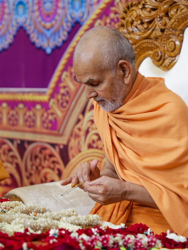 Swamishri applies chandan on a tilakiyu at the beginning of his puja