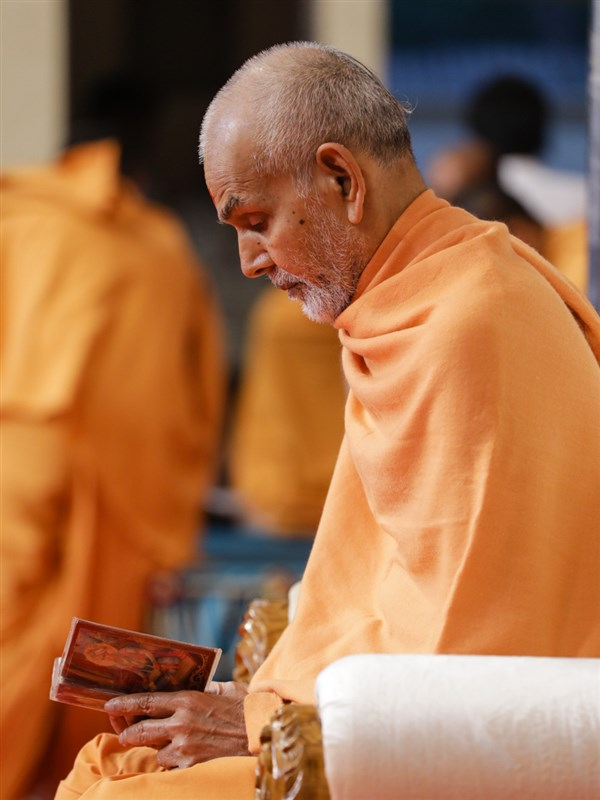Swamishri reads the Shikshapatri at the conclusion of his puja