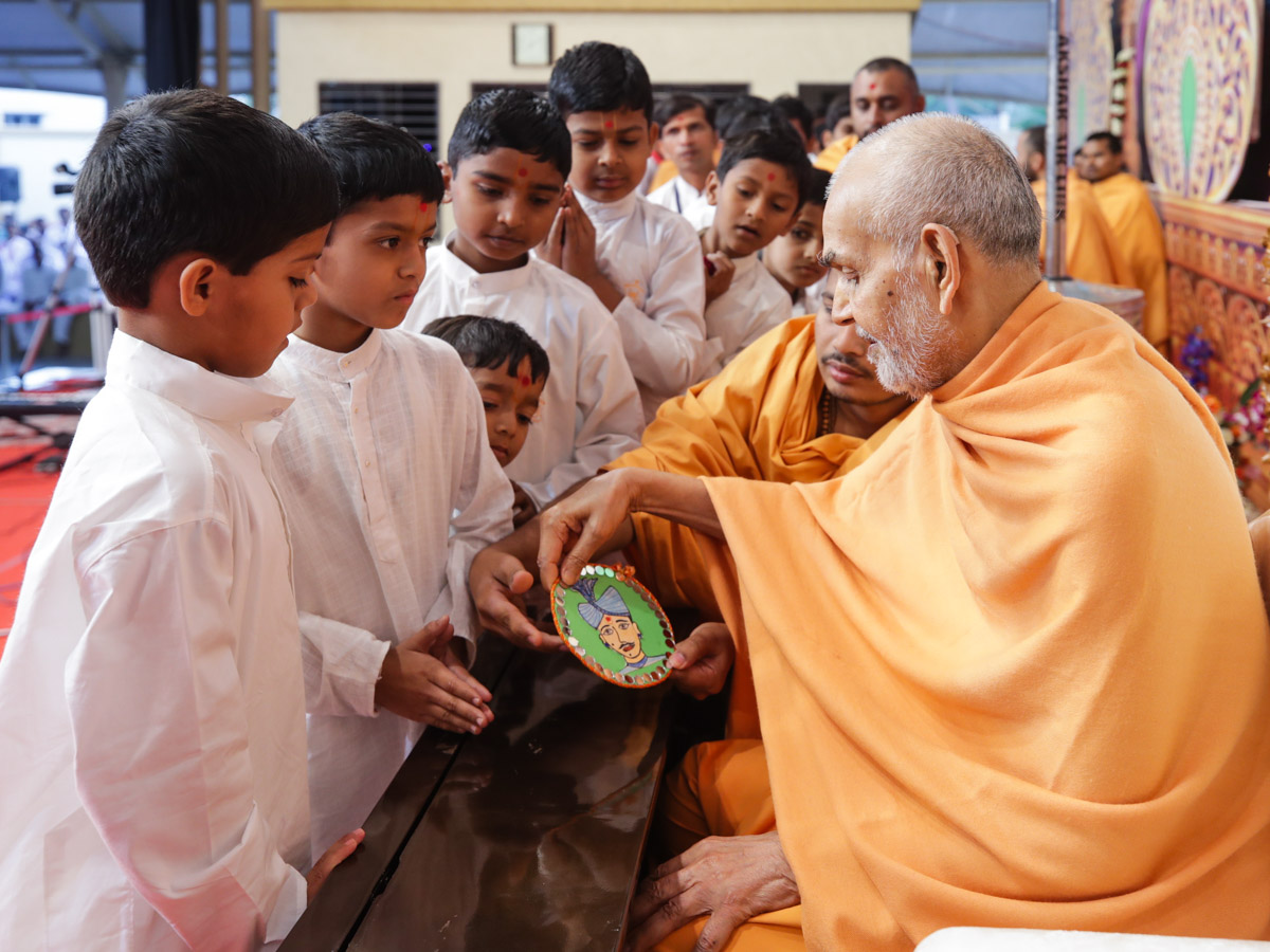 Swamishri observes a painting by a child