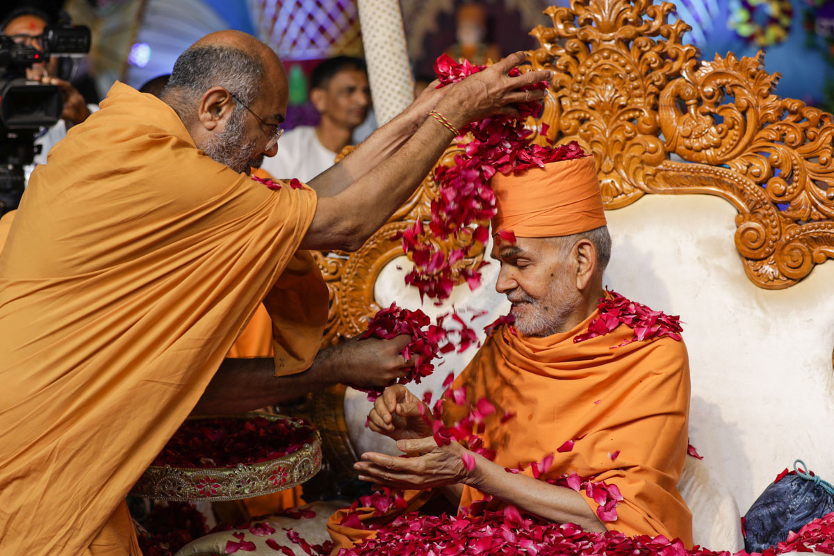 Dharmacharan Swami showers flower petals on Swamishri