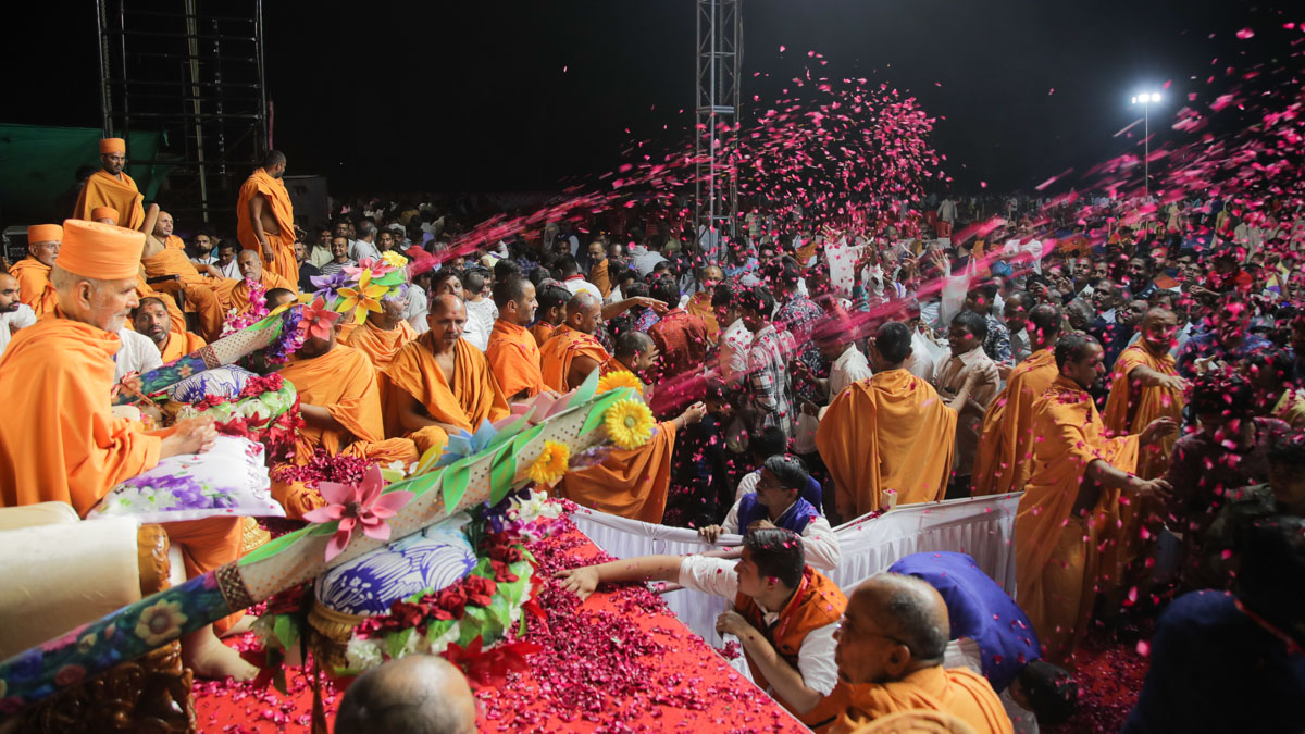 Devotees showered with sanctified flower petals as they pass by Swamishri