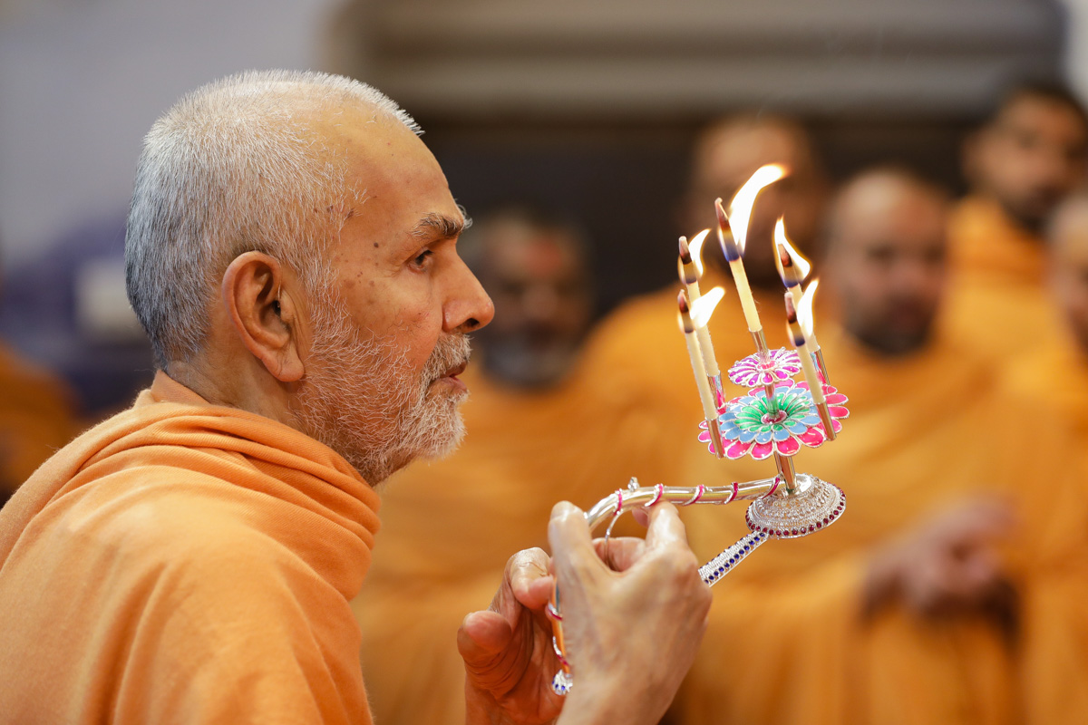 Swamishri performs the morning arti in the abhishek mandapam