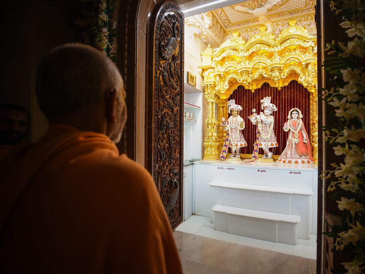 Swamishri engrossed in darshan of Shri Harikrishna Maharaj and Shri Radha-Krishna Dev