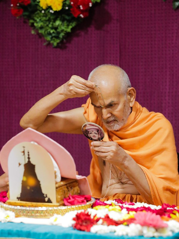 Swamishri applies tilak on his forehead at the beginning of his puja