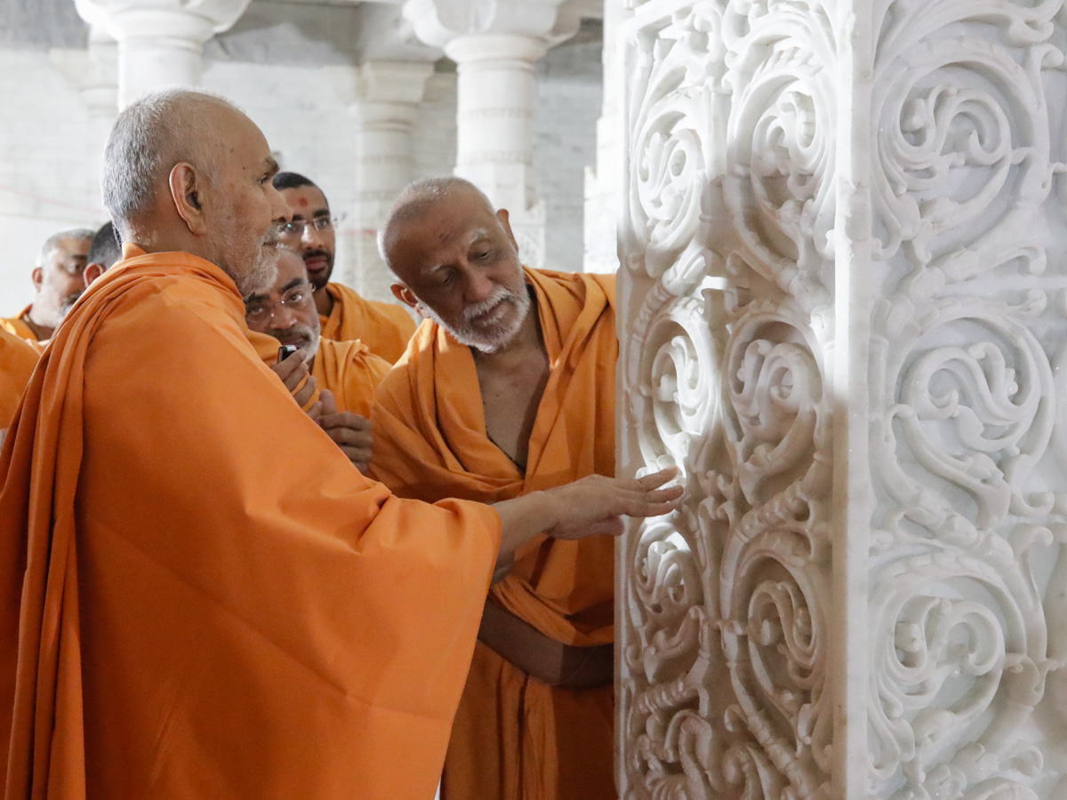 Swamishri observes the carvings on a pillar