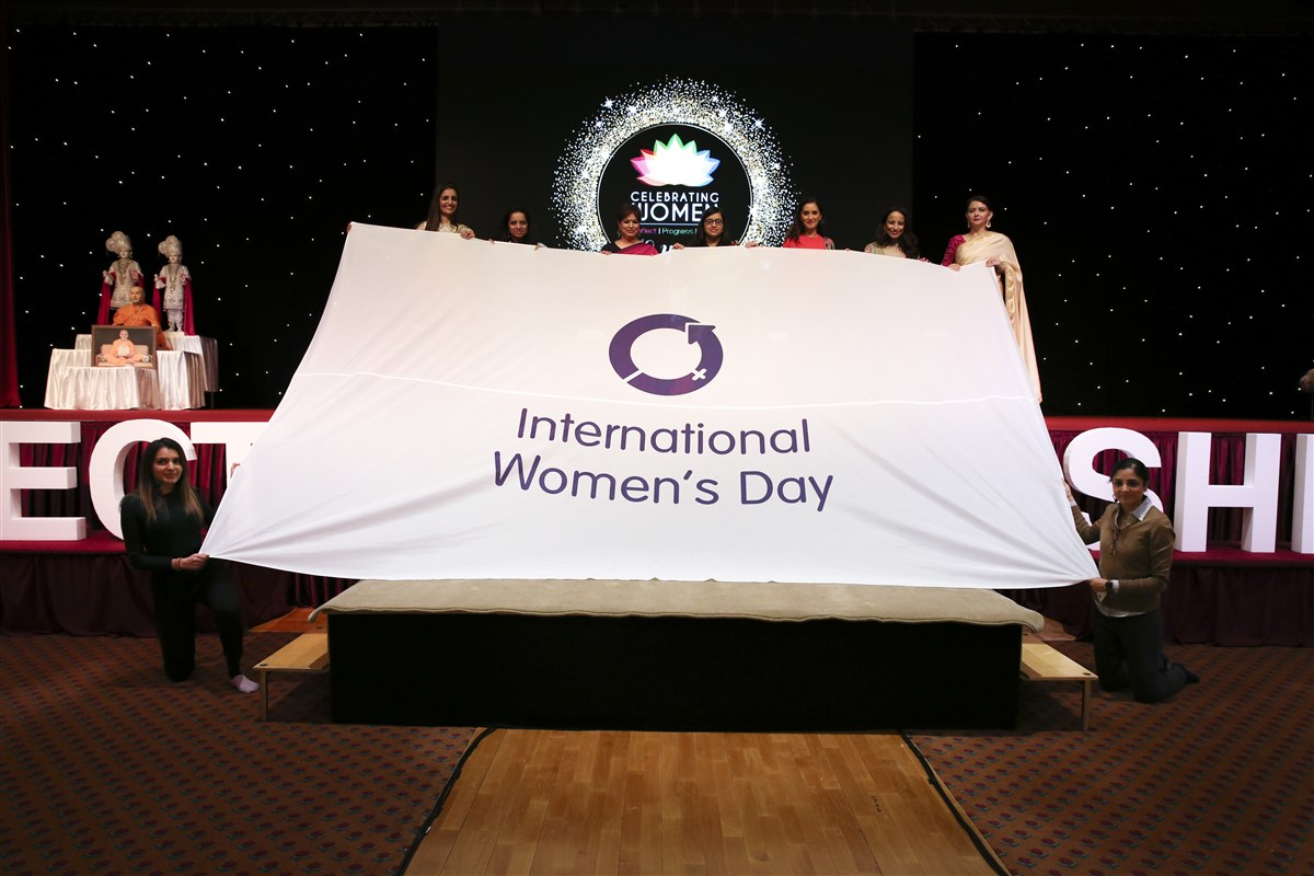 Distinguished guests holding the International Women's Day flag