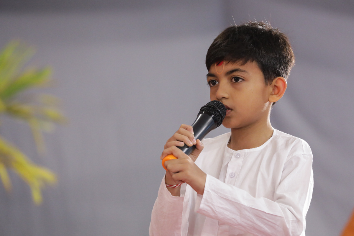 A child presents mukhpath during Swamishri's puja