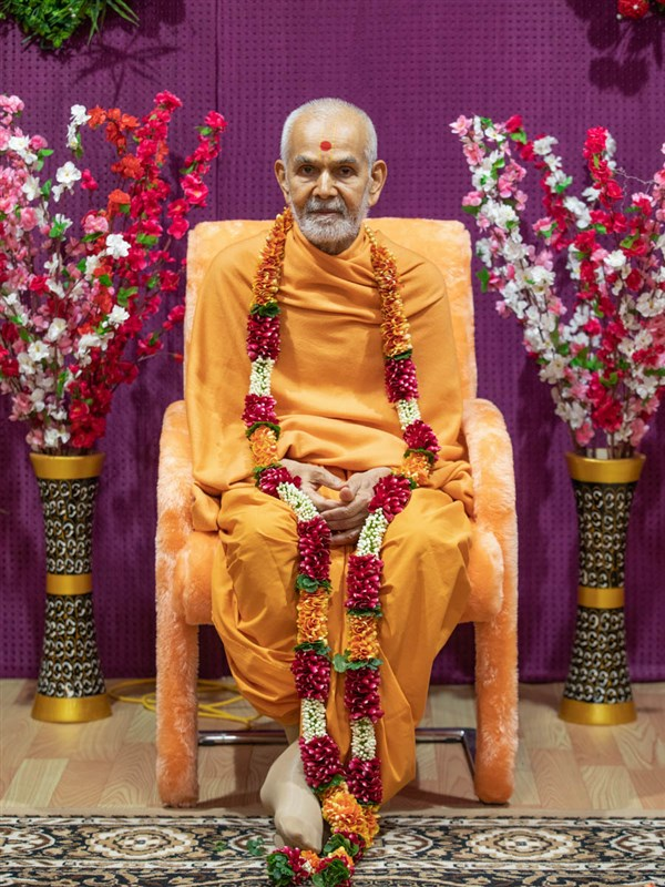 Swamishri honored with a flower garland