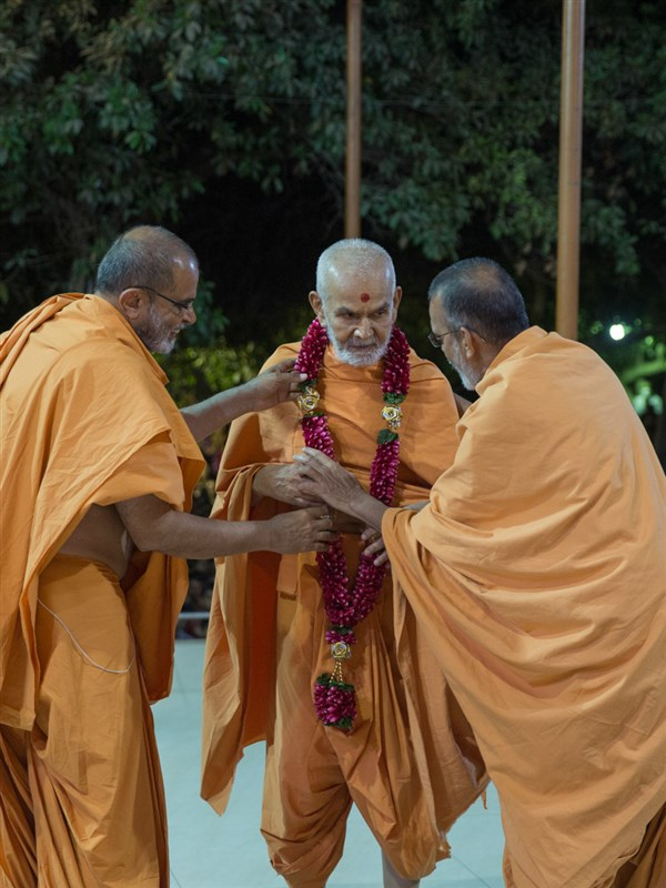 Gnaneshwar Swami and Narayanmuni Swami welcome Swamishri with a garland
