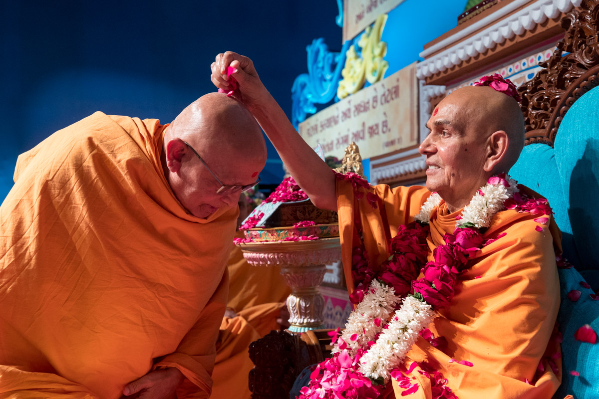Swamishri  showers flower petals on Pujya Ghanshyamcharan Swami