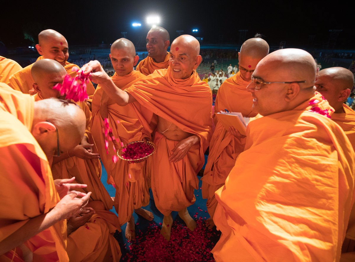 Swamishri showers flower petals on sadhus