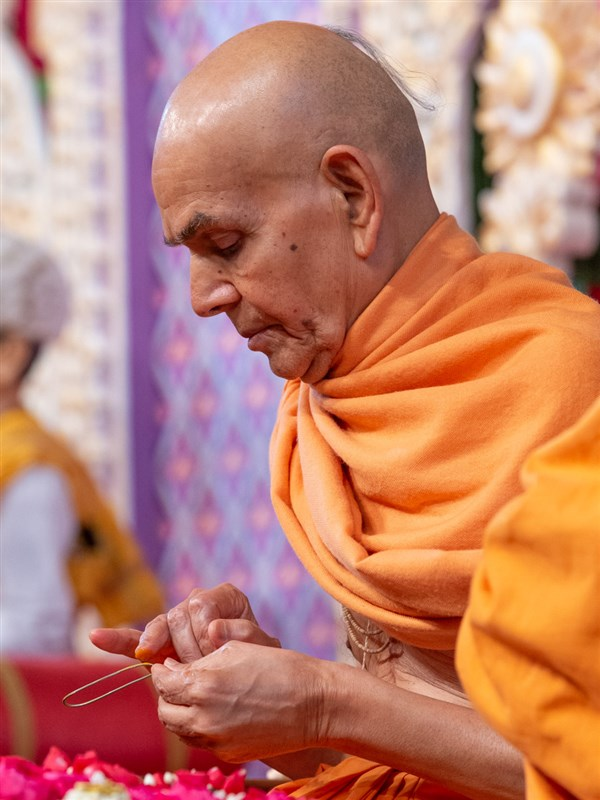 Swamishri applies chandan on a tilakiyu in his daily puja