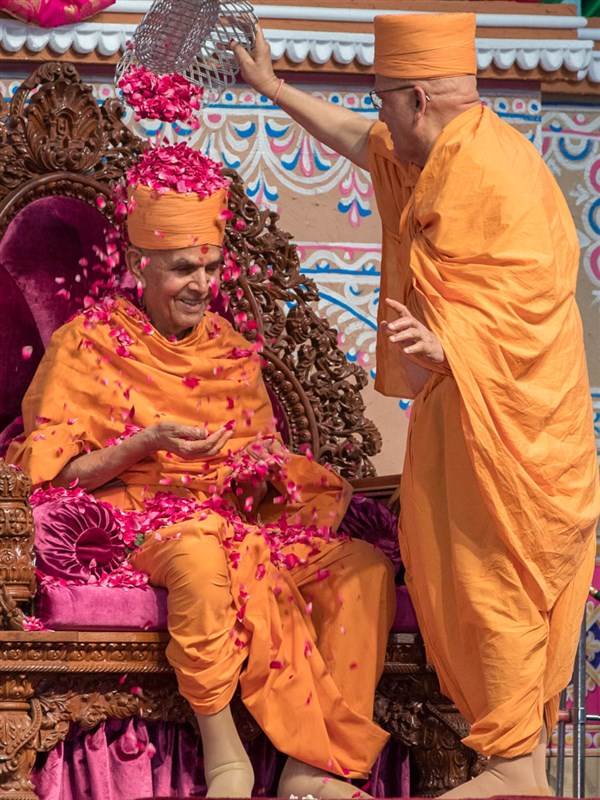 Pujya Ghanshyamcharan Swami shower flower petals on Swamishri