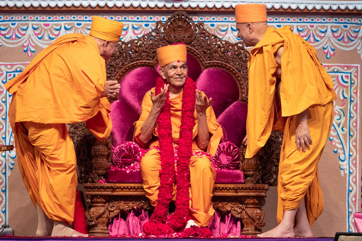 Pujya Ishwarcharan Swami and Pujya Viveksagar Swami honor Swamishri with a rose garland