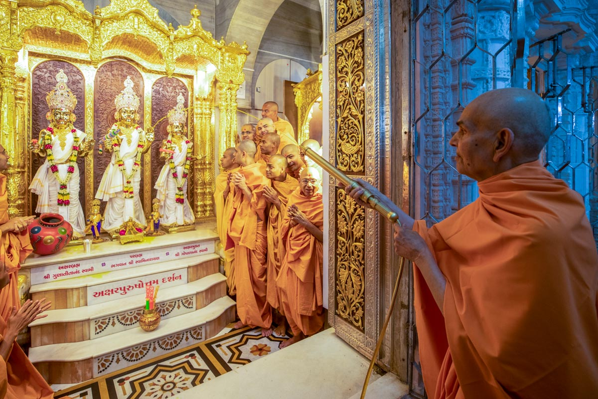 Swamishri sprays saffron-scented water on Thakorji