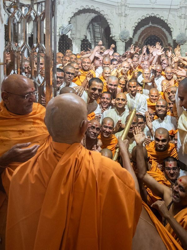 Swamishri sprays saffron-scented water on sadhus, parshads and sadhaks