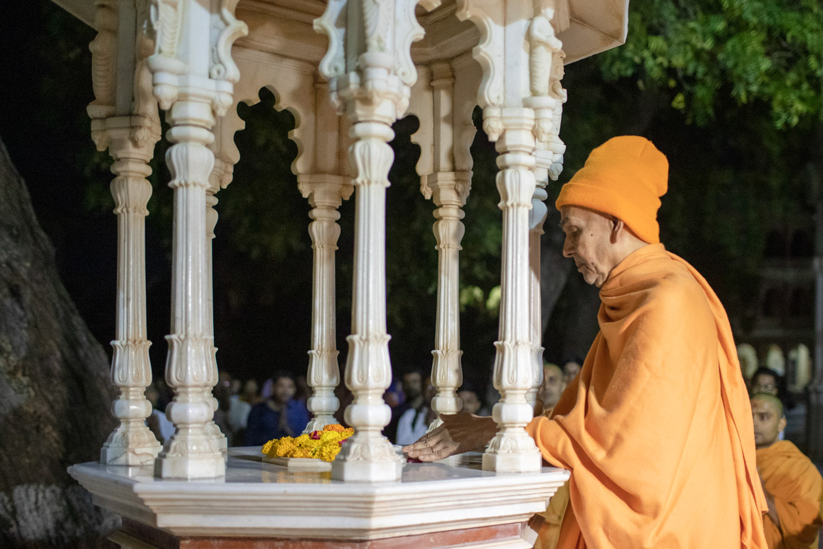 Swamishri engrossed in the darshan of the holy charanarvind of Bhagwan Swaminarayan in the mandir grounds