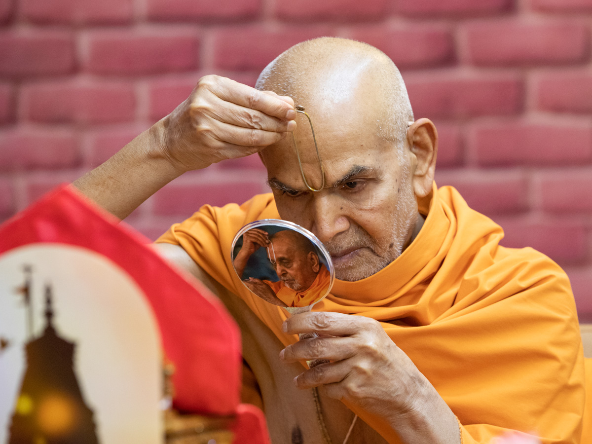 Swamishri applies tilak on his forehead in the beginning of his daily puja