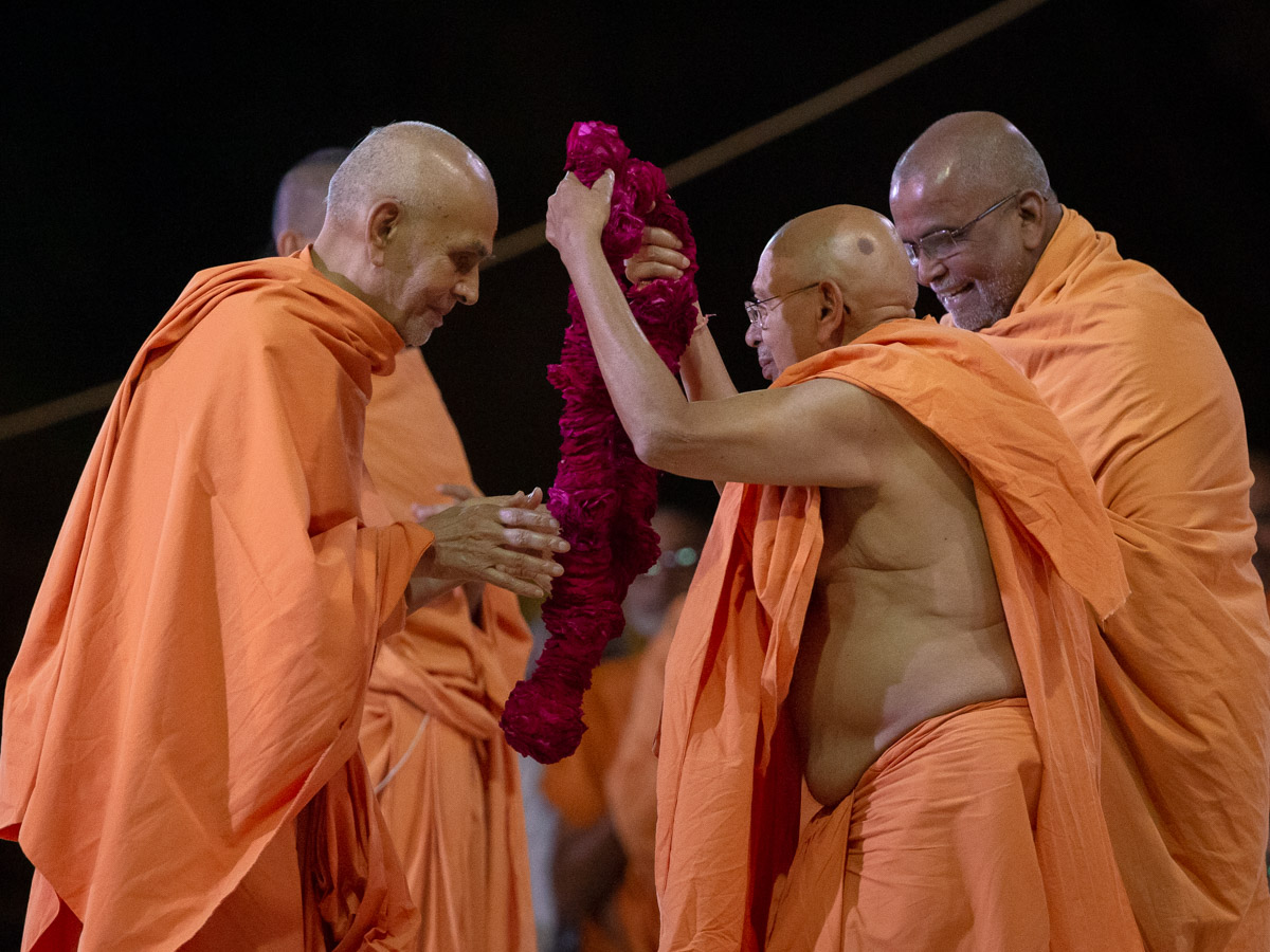 Pujya Tyagvallabh Swami honors Swamishri with a rose garland