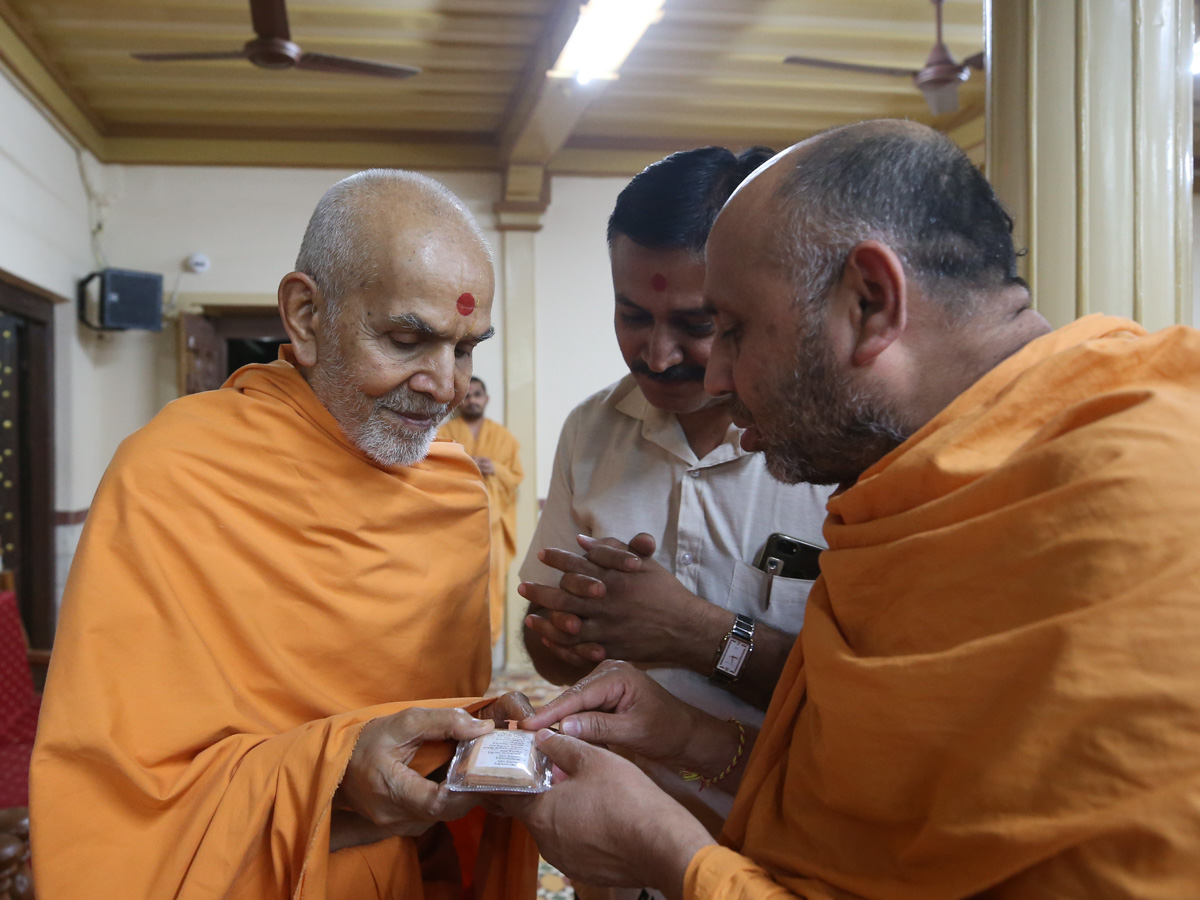 Swamishri doing darshan of a holy relics