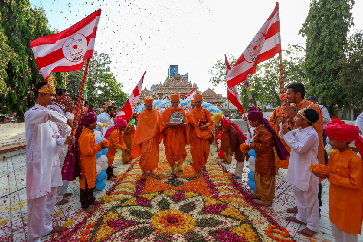 Children welcome Swamishri with flower petals and flags